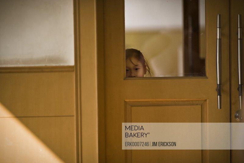 Girl peeking through the doors of a gym.
