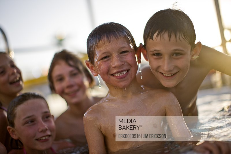 Portrait of a smiling boy in a swimming pool surrounded by his friends.