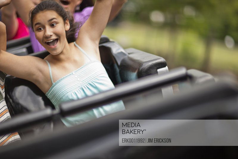 Happy people riding a rollercoaster at an amusement park.