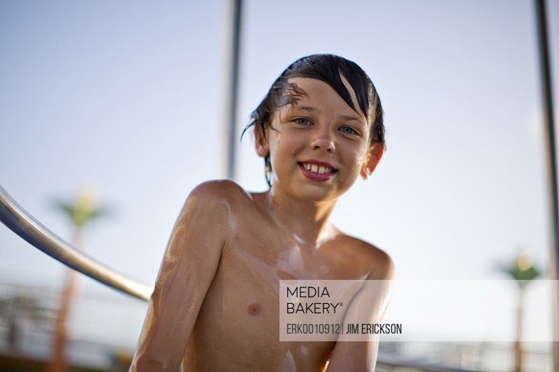 Portrait of a wet and shirtless young boy smiling.
