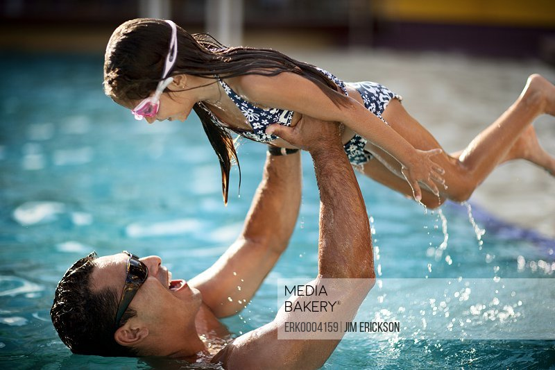 Father holds his daughter aloft at a swimming pool.