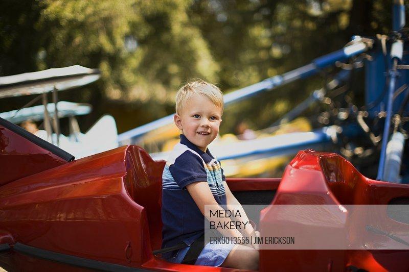 Boy sitting in airplane amusement park ride.