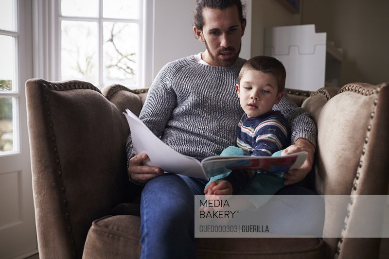 Father Sitting In Chair At Home Reading Story To Son