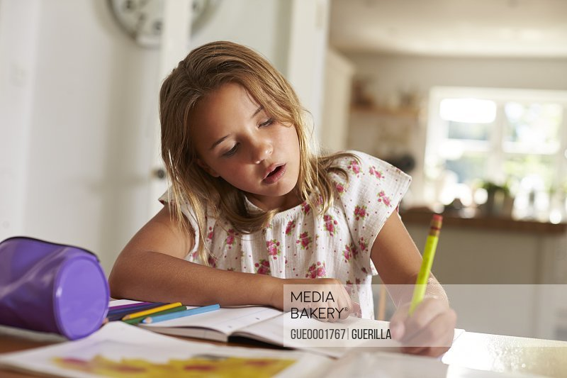 Girl concentrating on writing her homework