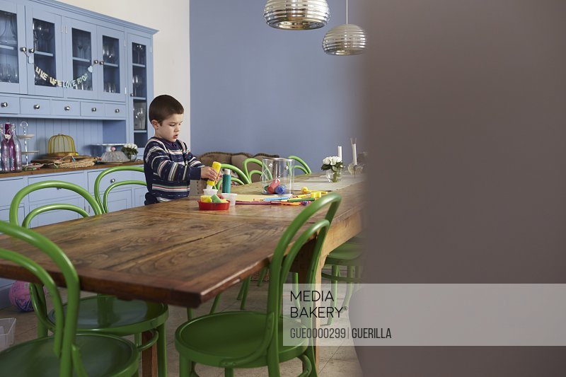Young Boy Sitting At Kitchen Table And Painting Picture