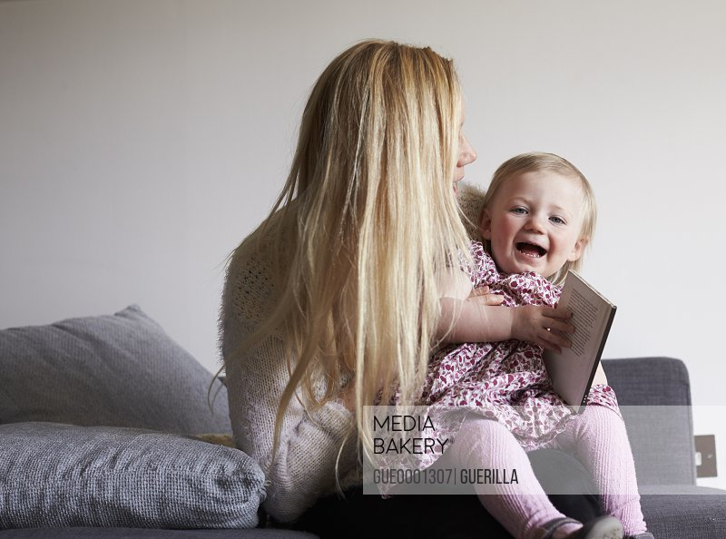 Mother Sitting On Sofa Reading Story With Daughter