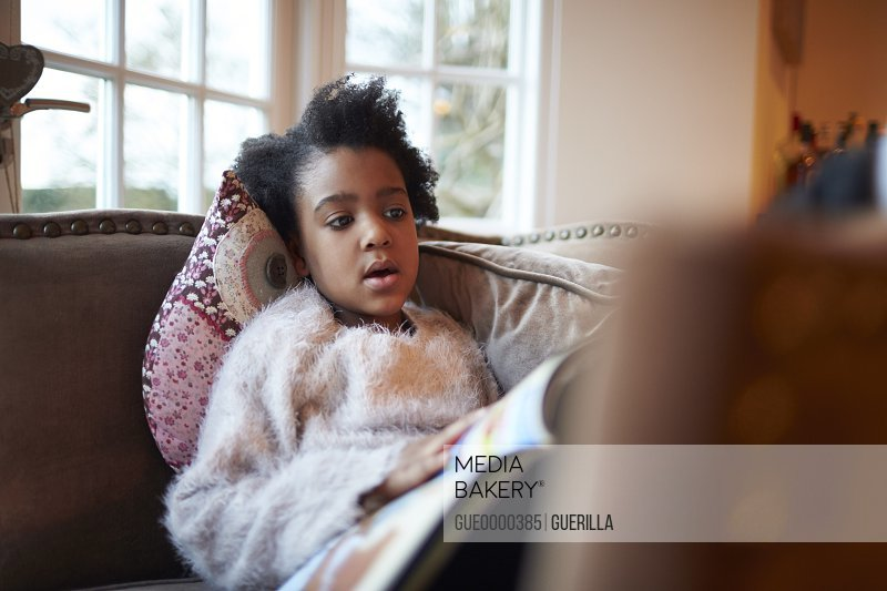 Young Girl Reading Book On Sofa At Home
