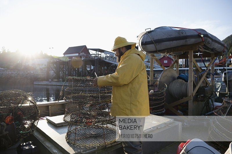 Fisherman preparing cages and equipment on dock