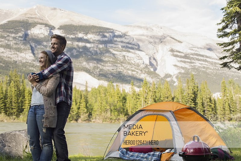 Couple hugging outside campsite at lakeside