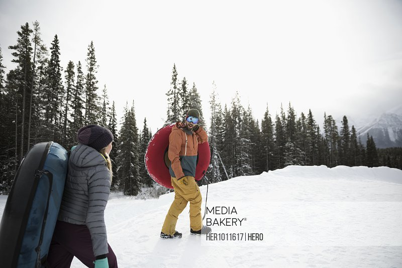 Couple with inner tubes climbing snowy hill