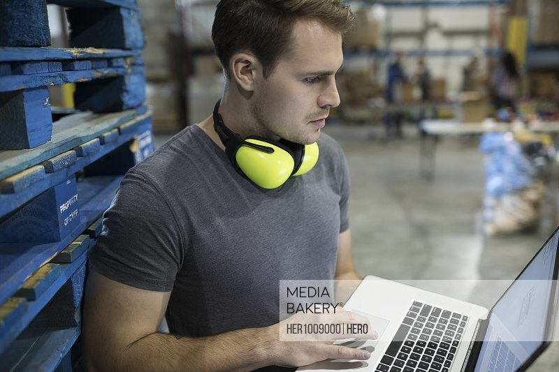 Focused male worker using laptop in distribution warehouse
