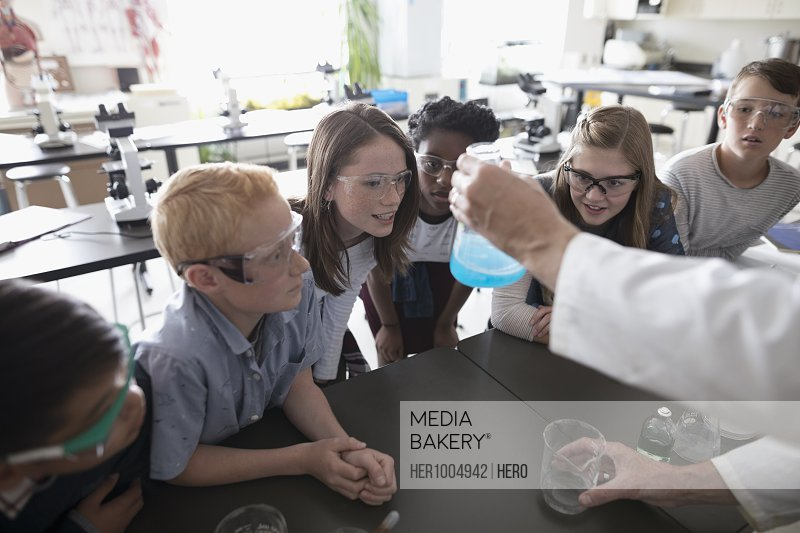 Teacher and middle school students conducting scientific experiment in science laboratory