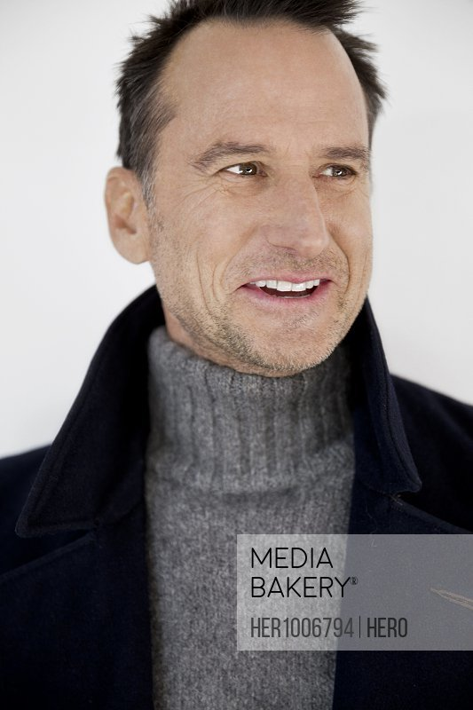 Portrait smiling mature man in turtleneck sweater and collared coat against white background