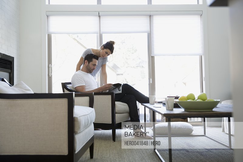 Couple reading magazine in living room
