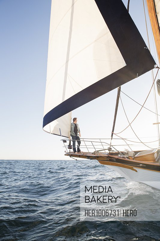 Man sailing on sailboat on sunny ocean