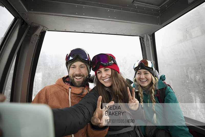 Skier friends riding gondola, posing for selfie with camera phone
