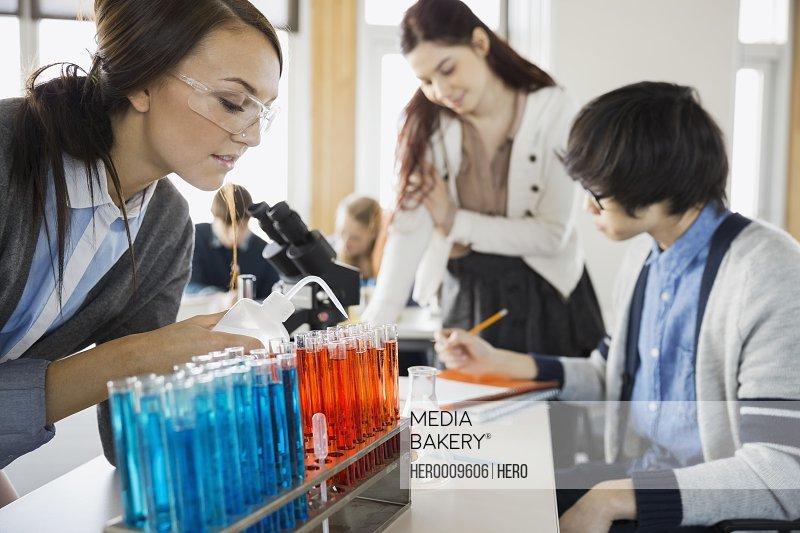 High school students conducting scientific experiment in classroom