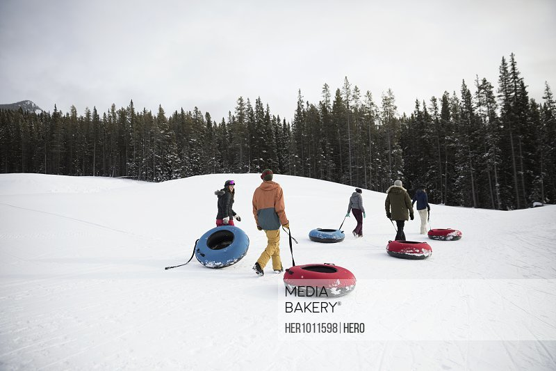 Friends carrying inner tubes in snow