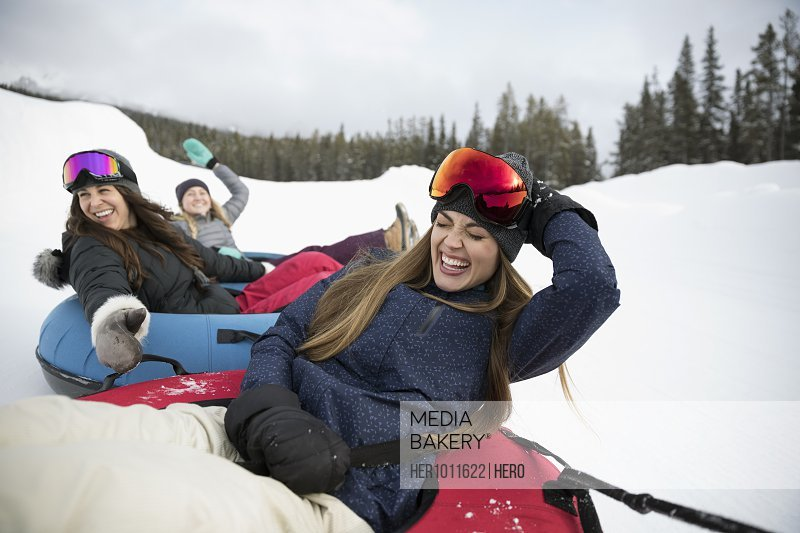 Playful female friends riding inner tubes in snow