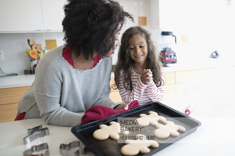 Mother and daughters baking Christmas gingerbread cookies in kitchen