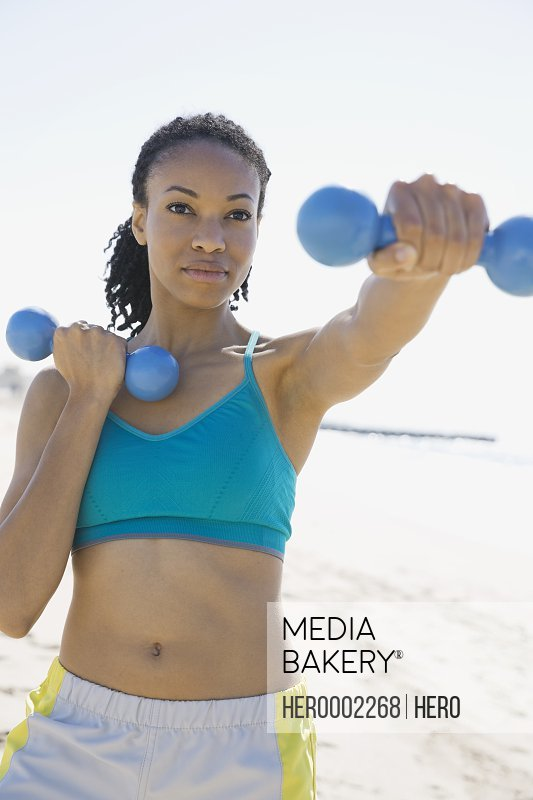 Woman lifting dumbbells on beach