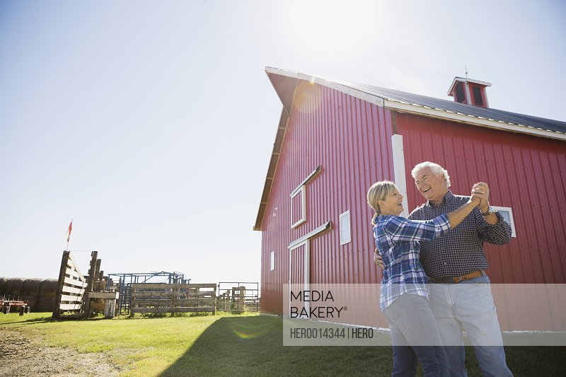 Senior couple smiling outside barn on farm