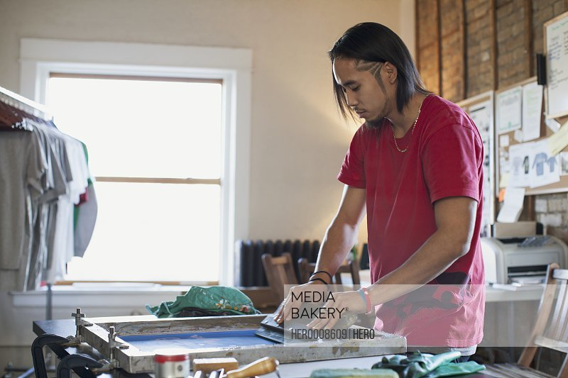 Man using silk screen for T-shirt printing at workshop