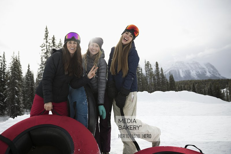 Portrait playful female friends with inner tubes in snow