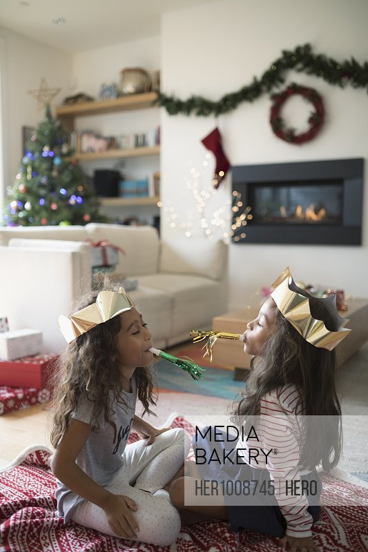 Sisters in paper Christmas crowns playing with party favors in living room