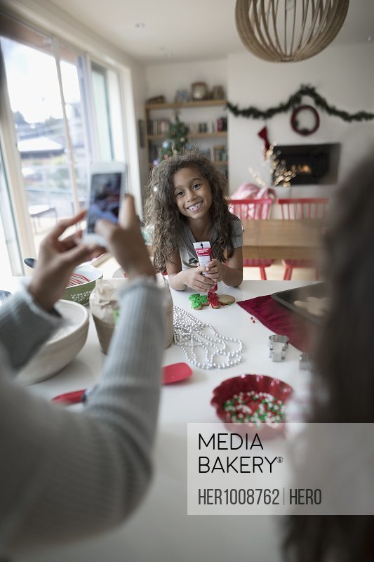 Mother with camera phone  photographing daughter decorating Christmas gingerbread cookies in kitchen