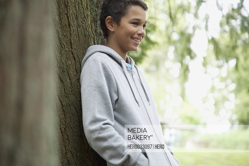 pre-teen learning on tree outdoors