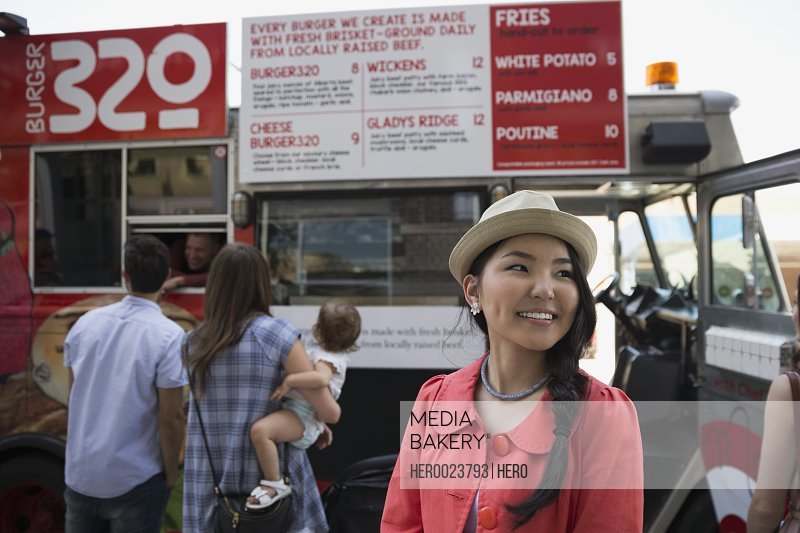 Smiling woman in hat outside food truck