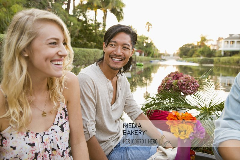 Smiling couple on raft with flowers on summer lake