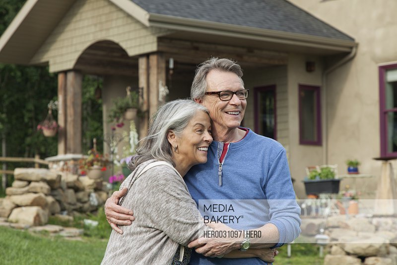 senior couple hugging outside their country home