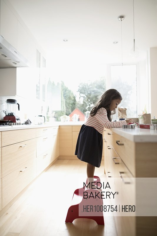 Girl on step stool decorating cookies at kitchen counter