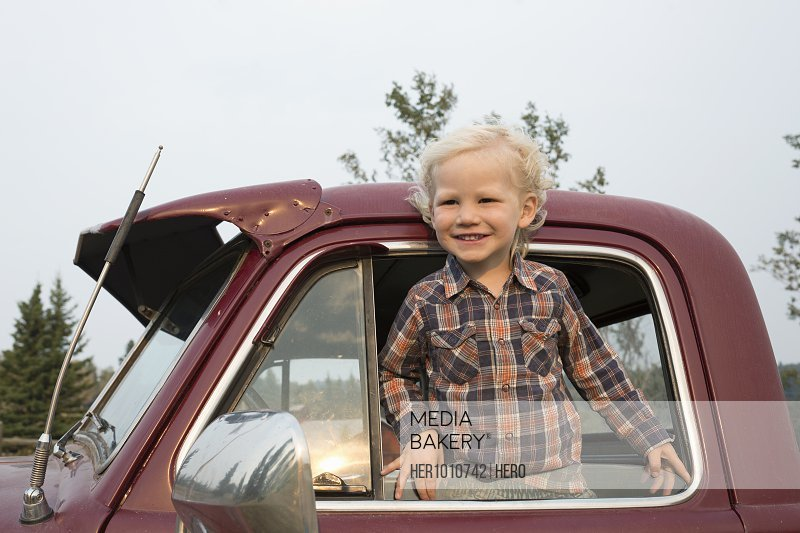 Portrait smiling, happy blonde boy in truck
