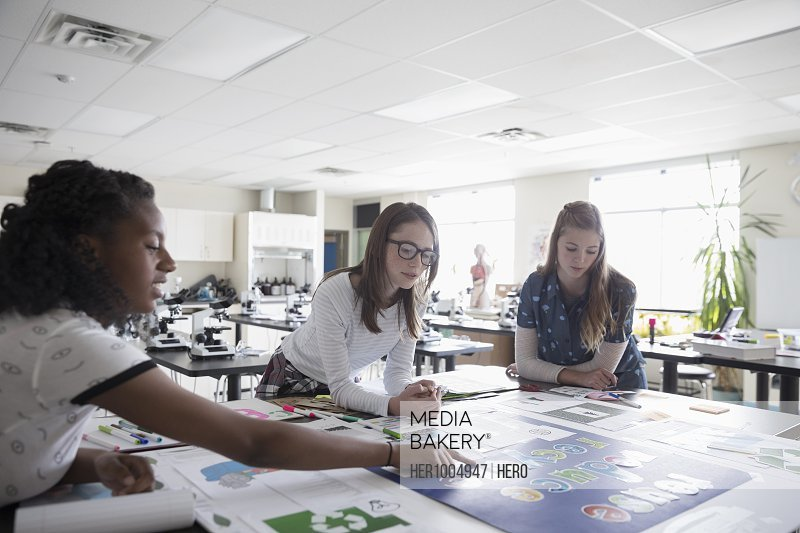 Girl middle school students working on science project in classroom