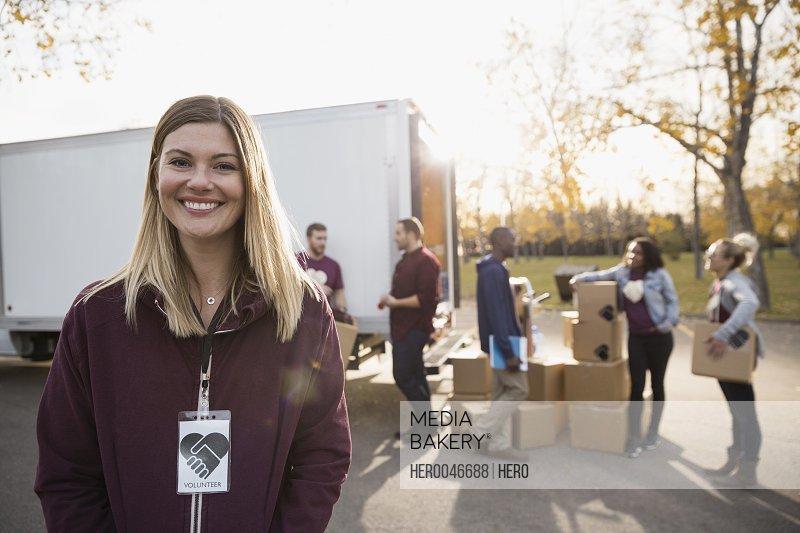 Portrait smiling female volunteer standing outside truck