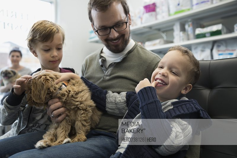 Father and laughing sons with dog veterinarian lobby