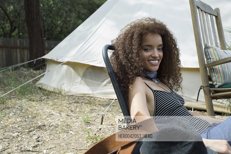 Portrait smiling young woman outside camping yurt