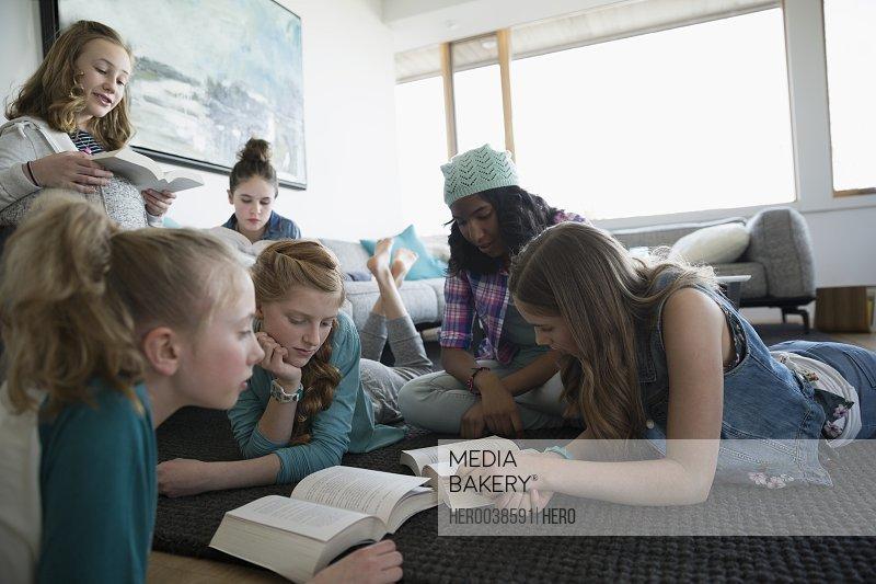 Girls reading books in living room