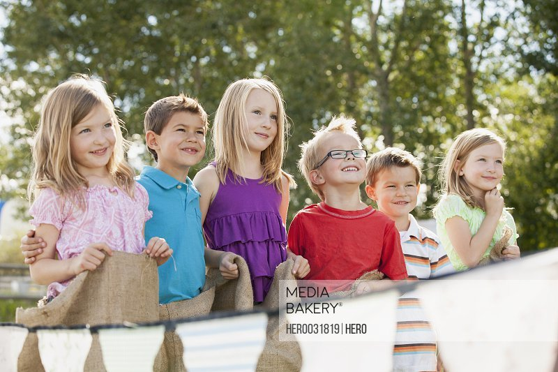 Young cousins waiting to start potato sack race
