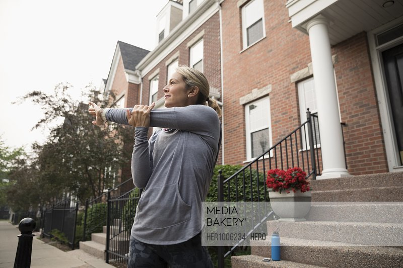Female runner stretching arm outside brownstone