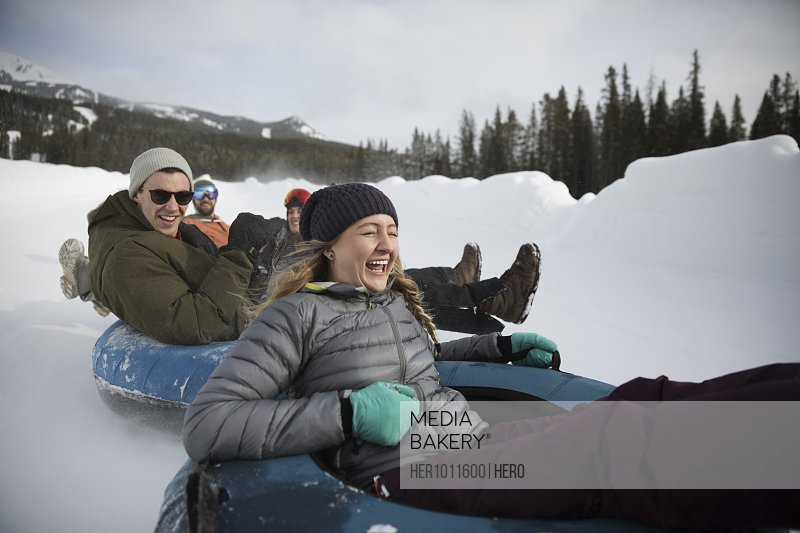 Playful, happy friends riding inner tubes in snow