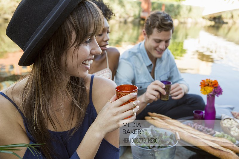 Smiling young woman drinking, enjoying picnic with friends on summer lake