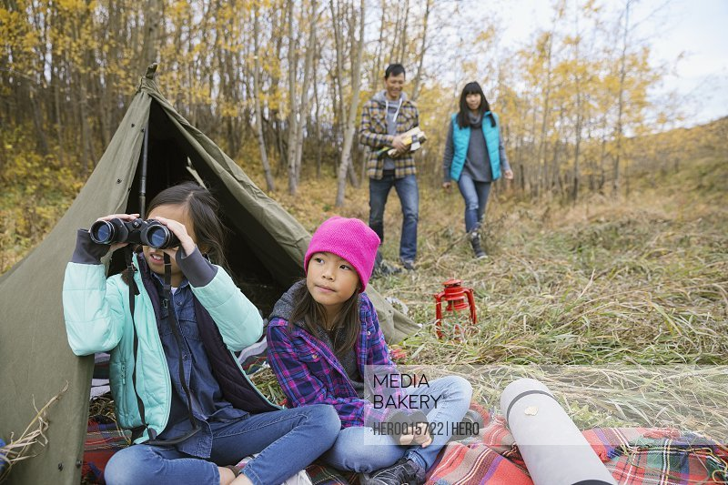 Sisters with binoculars outside tent