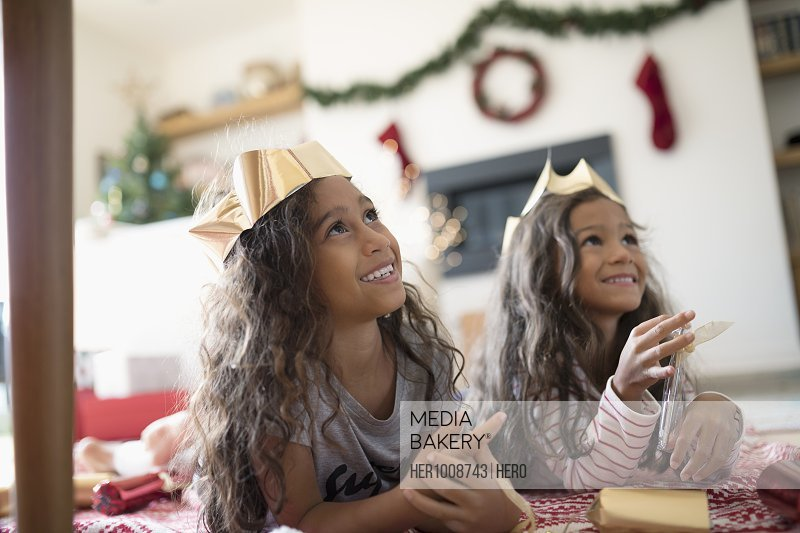 Smiling sisters wearing paper Christmas crowns, looking up in living room