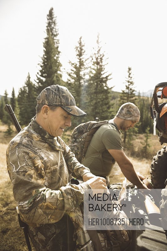 Father and son hunters preparing hunting equipment