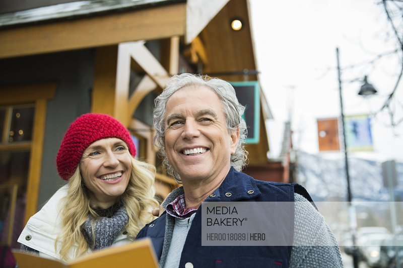 Smiling couple with map outside storefront