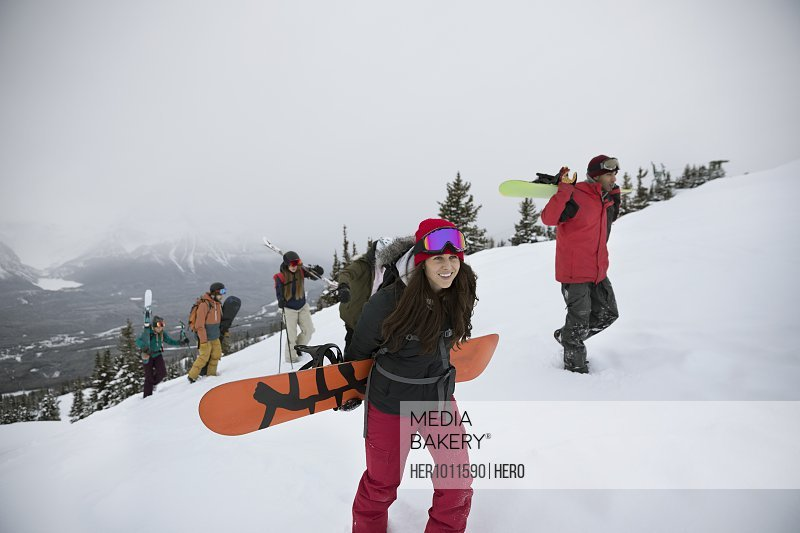 Skiers and snowboarders hiking snowy hill